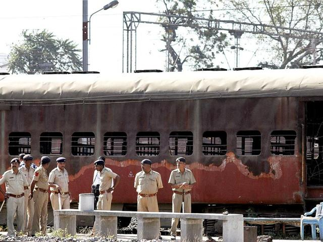 Policemen stand guard near the charred bogie of the  Sabarmati Express at Godhra railway station.