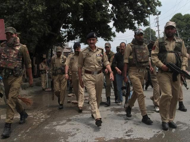 Police officials gather at the site of an attack by suspected militants in Srinagar.(Waseem Andrabi/HT Photo)