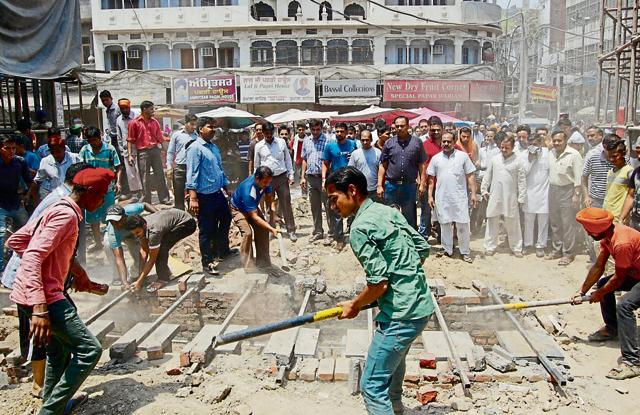 Shopkeepers destroying a structure constructed for installing bollards near the Golden Temple.