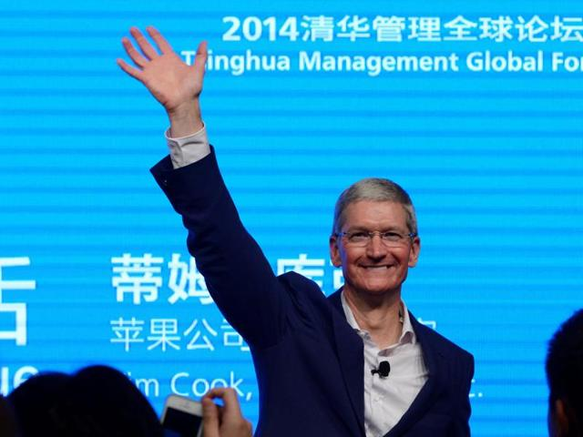 Apple CEO Tim Cook waves as he attends a talk in Beijing.