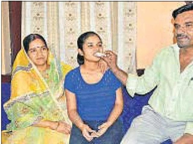 Jharkhand Class 12 CBSE board examination topper Diksha Sharma celebrates with her parents in Dhanbad on Saturday.