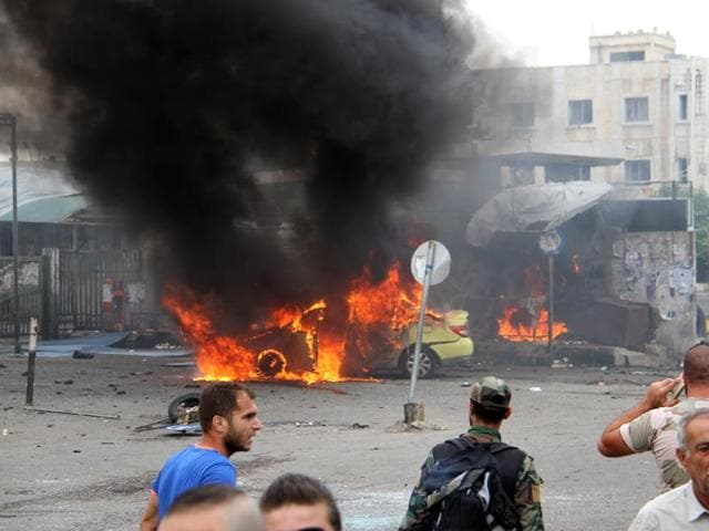 Syrians gather in front of a burning car at the scene where suicide bombers blew themselves up, in the coastal town of Tartus on Monday.