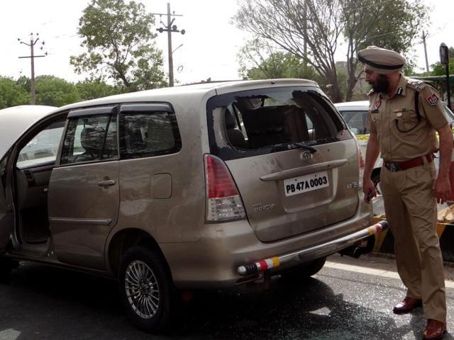 DIG Yurinder Singh Hayer next to the Toyota Innova from which robbers took away Rs 60 lakh in Moga on Monday.