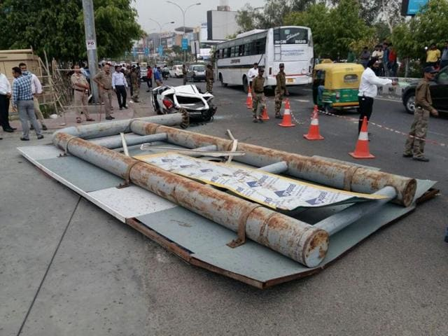 A giant signboard fell during a storm on  a car and a bike passing by outside DLF mall, Sector 18, Noida on Monday.