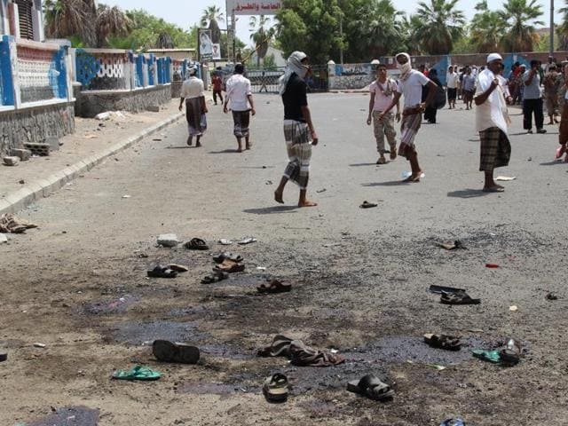 People gather at the scene after a pair of suicide bombings attack in the southern city of Aden, Yemen, on Monday.
