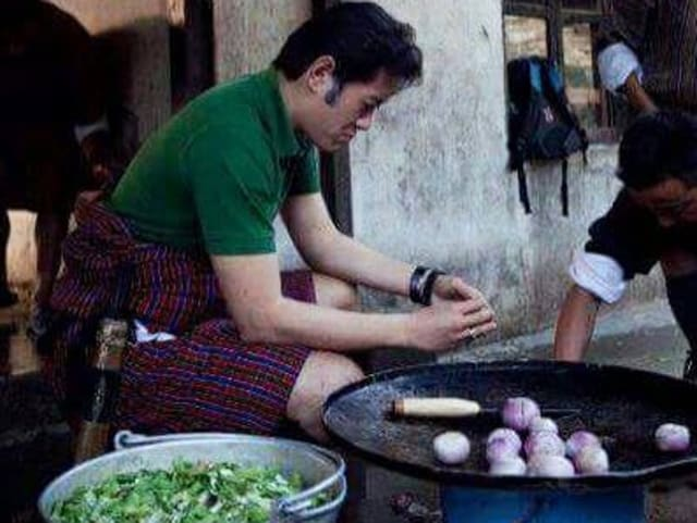 King of Bhutan chopping onions and chilli to prepare a meal for the community school in Mongar.