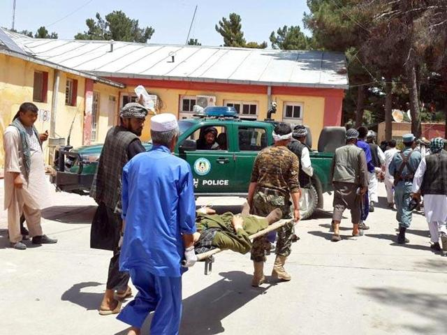 Afghan men carry a man injured in a bomb blast in Faryab province.