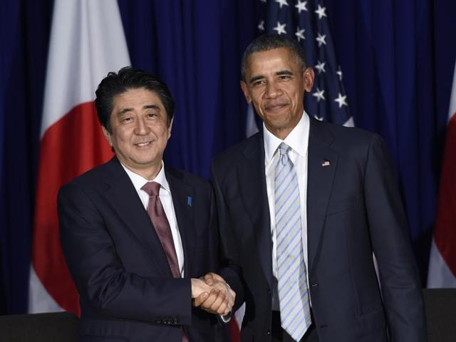 US President Barack Obama, right, and Japan's Prime Minister Shinzo Abe, left, shake hands during a bilateral meeting at the Asia-Pacific Economic Cooperation summit in Manila, Philippines.