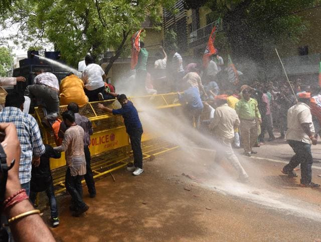 Delhi police fire water cannons to disperse BJP workers during their protest over water shortage and power cuts, outside Delhi CM Arvind Kejriwal's residence on Tuesday.