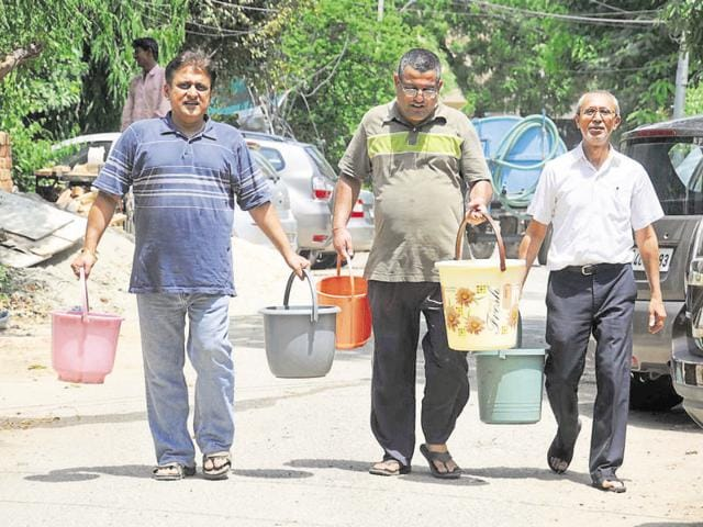 Residents of DLF City Phase 1 Block E carry water from a tanker.