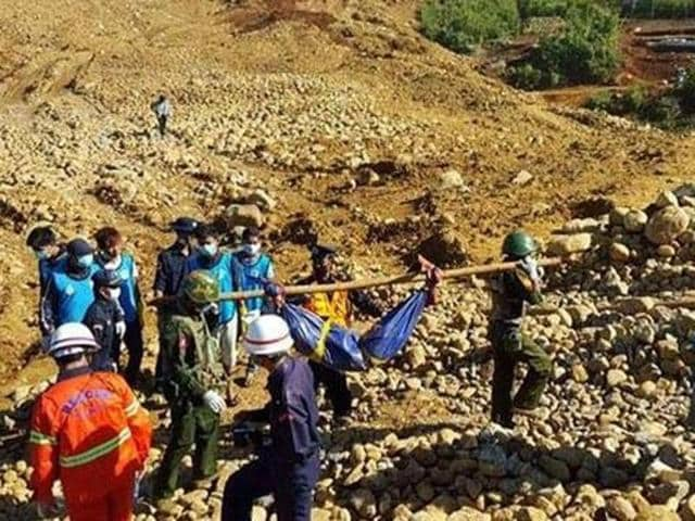 Soldiers carry a body of a miner killed in a landslide in a jade mining area in Hpakhant, Myanmar.