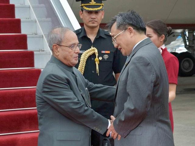 President Pranab Mukherjee is received by Vice Governor of Guangdong He Zhongyou as China's Foreign Affairs Vice Minister Liu Zhenmin looks on, upon his arrival at Guangzhou in China on Tuesday.