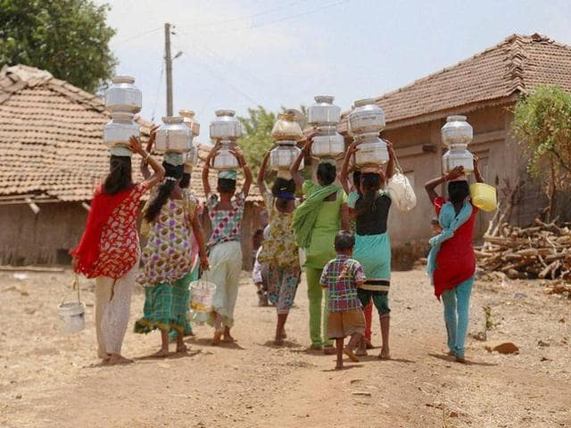 A girl carries drinking water in a plastic container on her head as she walk back to her village after collecting it from an almost dried up well in Samba district, 40 kilometres from Jammu.