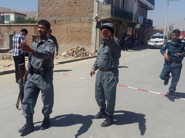 Afghan policemen try to cordon off the site of a suicide blast in Kabul.