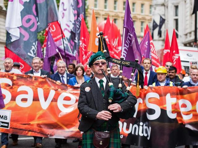 A piper plays as he leads steel workers during a protest march against Tata Steel through central London on May 25, 2016.