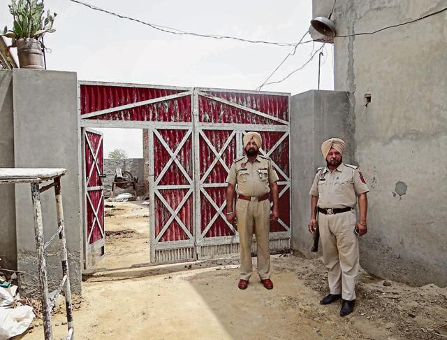 Cops deployed outside the house from where gangsters fled in a police vehicle at Butter Kalan village in Moga on Tuesday.