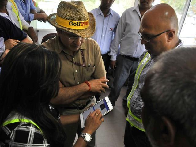 "NHAI Chairman Raghav Chandra (centre) watches demo oif the ""Highway Saathi"" app when he visited Kherki Daula Toll PLaza on May 14."