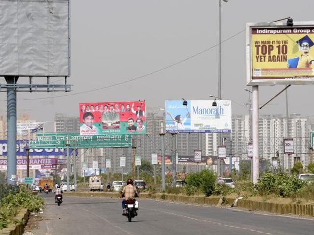 A giant billboard fell during a storm on a car and a bike passing by outside DLF Mall of India, Sector 18, Noida on Monday.