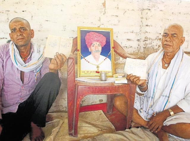 Mangidas's sons with their father's picture at their house in Bikaner's Jaimalsar village.