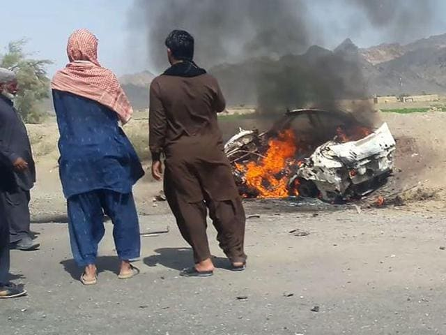 This photograph shows Pakistani local residents gathering around a destroyed vehicle hit by a drone strike in which Afghan Taliban chief Mullah Akhtar Mansour was believed to be travelling in the remote town of Ahmad Wal in Balochistan, around 160km west of Quetta.