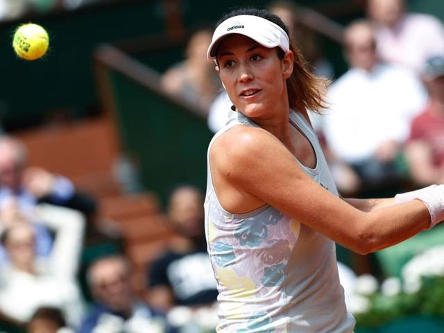Spain's Garbine Muguruza returns the ball to France's Myrtille Georges during their match.