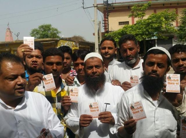 Muslims residents of Saharanpur flash their entry cards for Modi's rally.