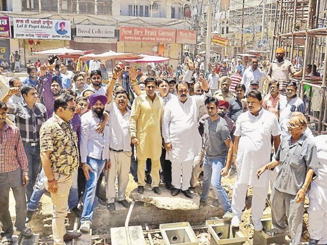 Rajya Sabha member Shwet Malik and traders raising slogans against the state government near the Golden Temple.