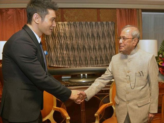 President Pranab Mukherjee shakes hands with Chinese film actor Huang Xiaoming at a meeting in Beijing, China.