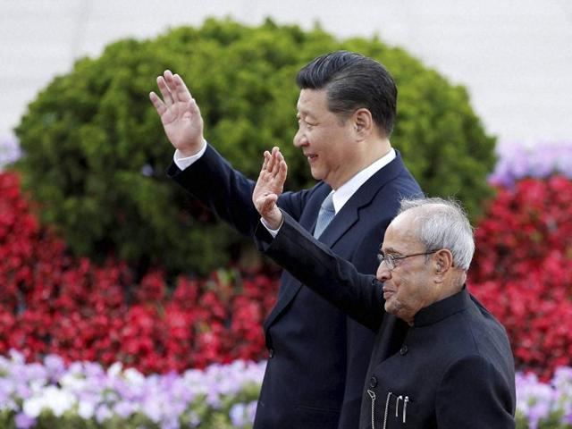President Pranab Mukherjee and Chinese President Xi Jinping wave during a welcome ceremony outside the Great Hall of the People in Beijing.