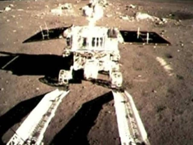 This image taken from a video, shows China's first moon rover touching the lunar surface and leaving deep traces on its loose soil.