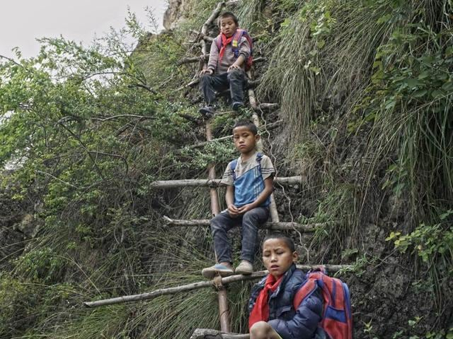 In this May 14, 2016 photo, children carrying their schoolbags take rest on the ladder built on a cliff in Zhaojue county, southwest China's Sichuan province.