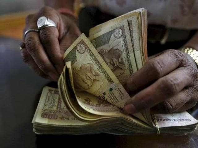 A money lender counts currency notes at his shop in Ahmedabad. the rupee appreciated 13 paise to 67.04 against the dollar in early trade on Friday