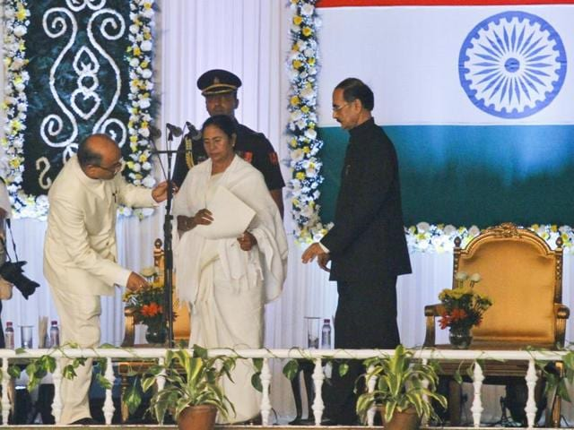 Officials adjust the microphone as Trinamool Congress party chief Mamata Banerjee prepares to take the oath of West Bengal chief ministership, in Kolkata on Friday.(AP)