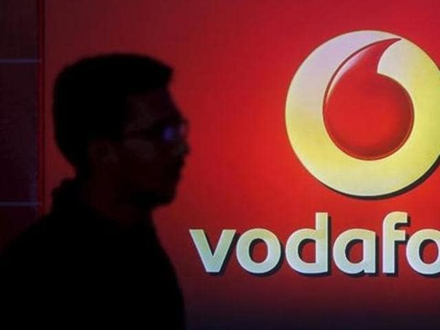A man casts a silhouette onto an electronic screen displaying a Vodafone logo, in Mumbai.