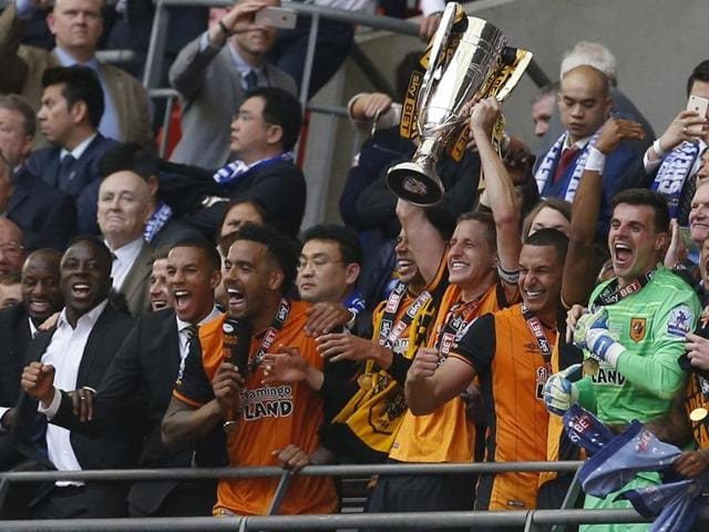 Hull City's Michael Dawson lifts the trophy as they celebrate winning promotion back to Premier League.