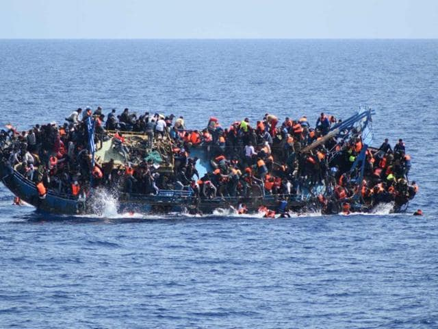 In this May 25, 2016 file combo, people try to jump in the water right before their boat overturns off the Libyan coast. Over 700 migrants are feared dead in three Mediterranean Sea shipwrecks south of Italy in the last few days .