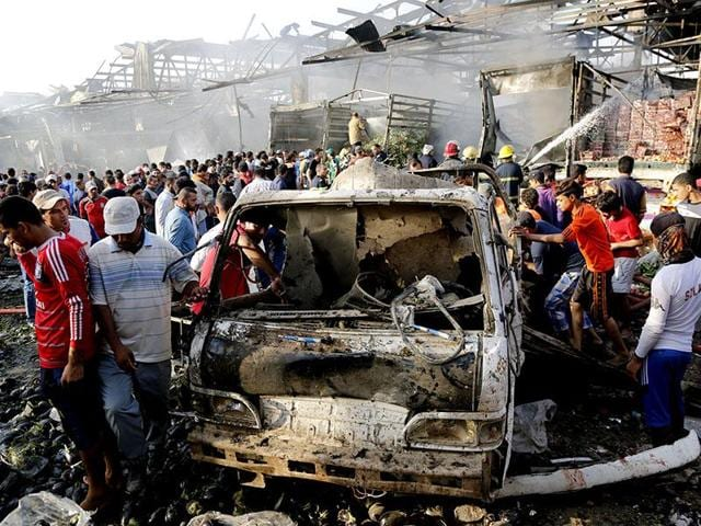 File photo of civilians at the scene of a suicide bombing at the northern neighborhood of Shula in Baghdad on July 27, 2016.
