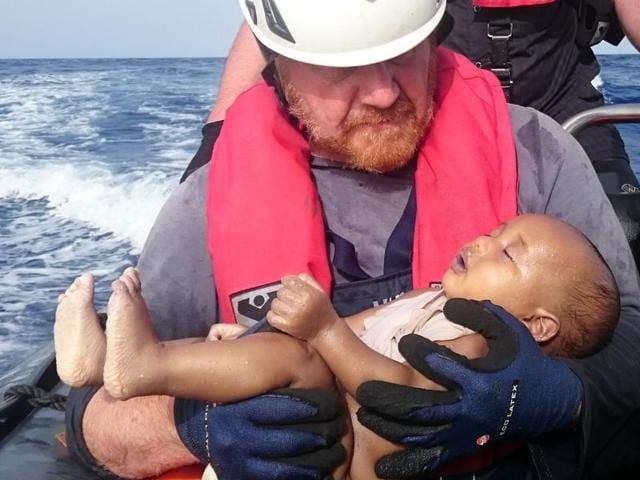 A German rescuer from the humanitarian organisation Sea-Watch holds a drowned migrant baby, off the Libyan cost May 27, 2016.