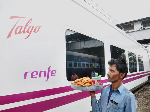 A vendor walks near the Spanish train Talgo after it arrives at Moradabad railway station during its first trial run between Bareilly and Moradabad on Sunday.