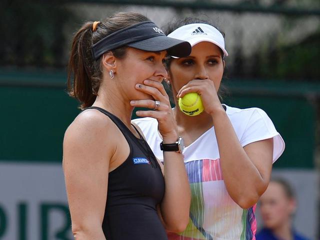 Martina Hingis speaks to Sania Mirza during their women's first round doubles match against Russia's Daria Kasatkina and Alexandra Panova.