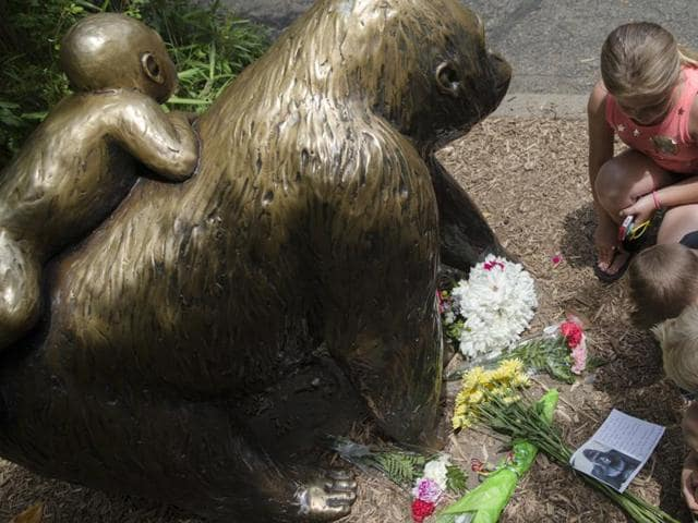 Children pause at the feet of a gorilla statue where flowers and a sympathy card have been placed, outside the Gorilla World exhibit at the Cincinnati Zoo & Botanical Garden.