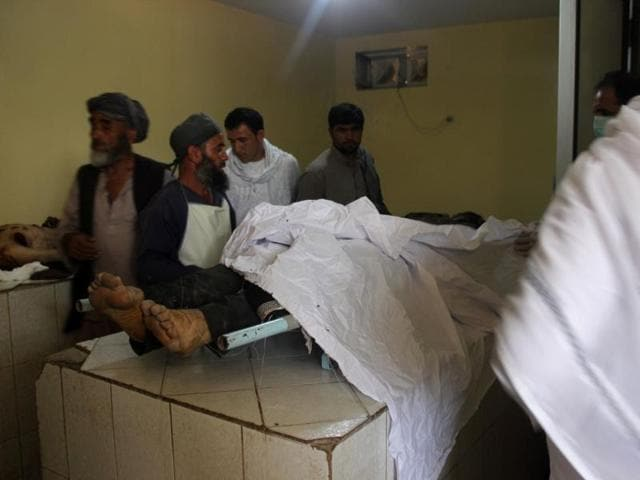 Afghan relatives stand over the body of the victim of a Taliban attack, in a hospital at the Aliabad district of Kunduz province.
