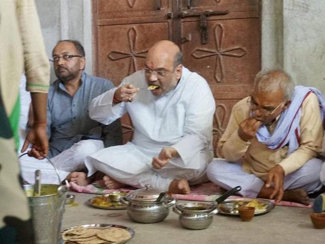 BJP President Amit Shah having a meal with a dalit family in Varanasi on Tuesday.