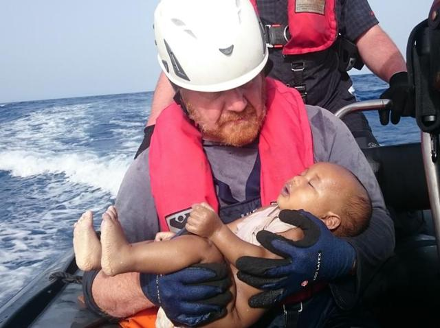 A Sea-Watch humanitarian organisation crew member holds a drowned migrant baby, during a rescue operation off the coasts of Libya.