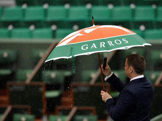 A spectator uses an umbrella as rain falls at the French Open.