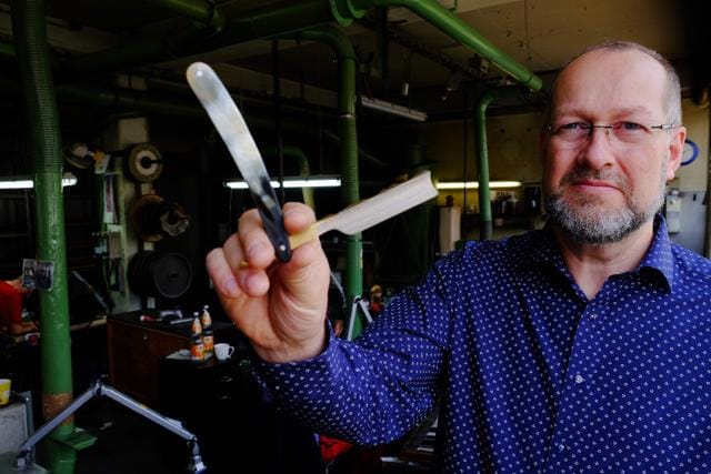 Managing director Ulrich Wiethoff poses in the factory of sizzle and razorblade manufacturer