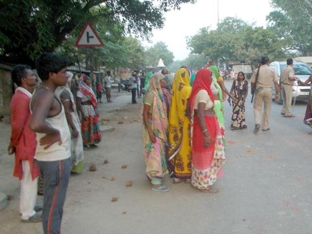 Villagers and policemen seen near the Azamgarh police station on Wednesday.