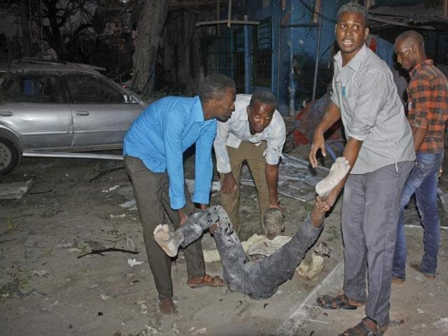 Somali men carry a wounded civilian who was injured in a bomb attack on an hotel in Mogadishu, Somalia Wednesday, June 1, 2016.