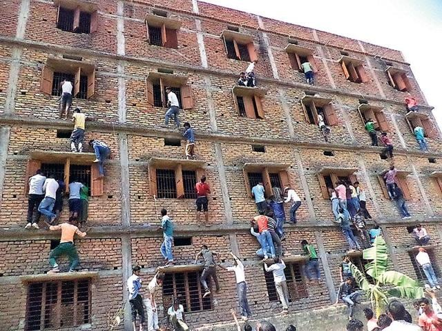 Family members and friends climb walls to make answer chits available to those appearing for their Class 10 exams at a centre in Vaishali, Bihar.