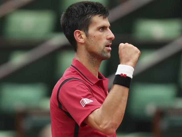 Novak Djokovic calls over a ball boy and teaches him his new post-match celebration after defeating Roberto Bautista Agut.